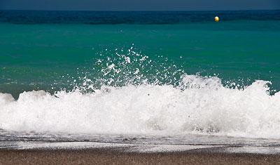 Vågor rullar in på Sabinillas strand