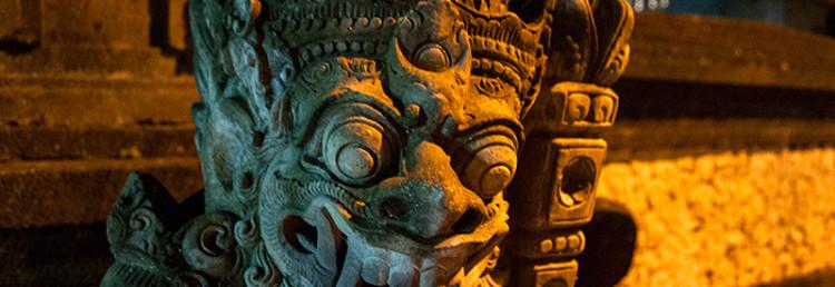 Demon staty i kvällsbelysning längs Sanur strandpromenad, Bali