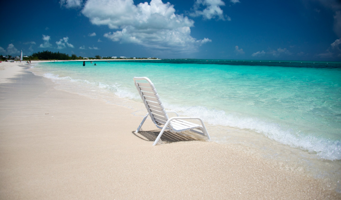 Strandstol i strandkanten. West Bay Club Resort, Turks & Caicos