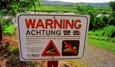 En skylt med varning för krokodiler i vattnet
