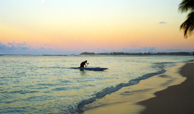 En man paddlar kanot in till Manase strand, norra Savai'i Samoa