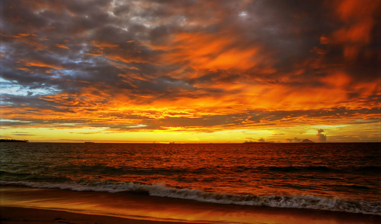 Magisk solnedgång med moln som glöder som eld vid ön Uoleva på Tonga