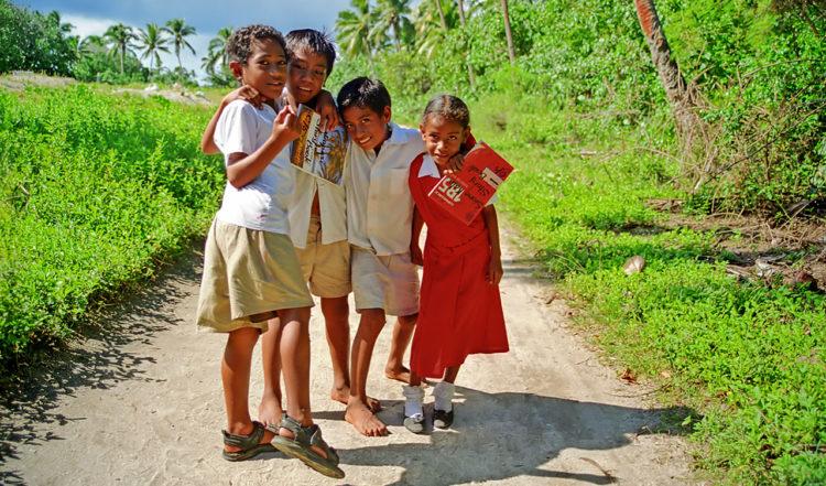 Glada skolbarn på väg mellan Uiha by och Felemea i Tonga
