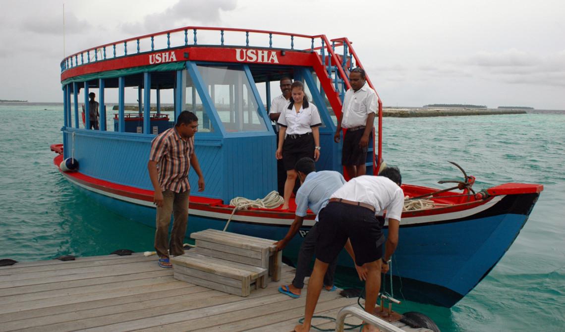 Vi går av på en pontonbrygga och går över på en Dhoni, en maldivisk båttyp