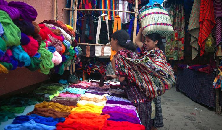 Kvinnor köper garn i klara färger på Chichicastenango Marknad, Guatemala