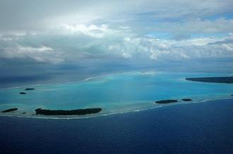 Vi får en fin vy över Aitutaki med alla små motus när vi lyfte med planet