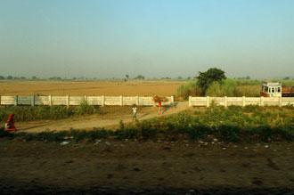 Utsikt över det indiska landskapet ifrån tåget mellan Delhi och Agra