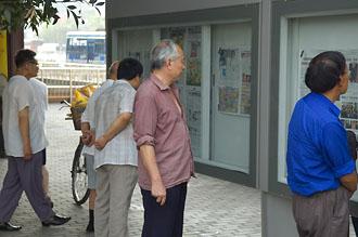 Kineser läser senaste nyheterna i tidningar uppsatta i montrar, Beijing