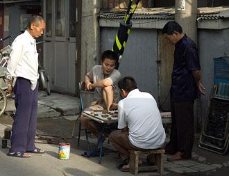 Kineserna är mycket för sällskapsspel, här tittar flera på vid ett pågående spel längstmed en gata bland hutongerna i Beijing