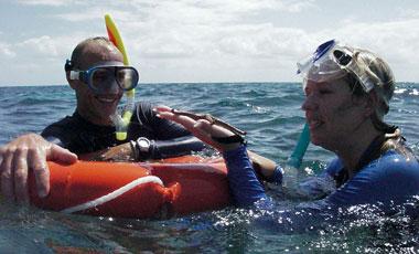 Anki håller sjöstjärna, vid snorkling i barriärrevet med Ocean Safari Tour