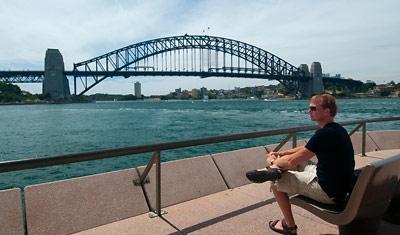 Lasse sitter vid Sydney operahus och blickar ut över Sydney Harbour bridge