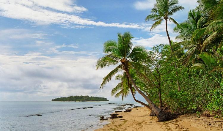 Strand på norra Uiha och lilla ön Tatafa alldeles bortom