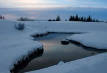 En vinterhimmel speglas i vattendrag vid Tingvalla, Island