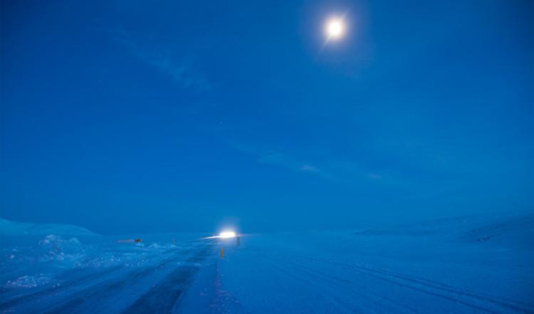 Månen lyser upp en isig vinterväg på Island