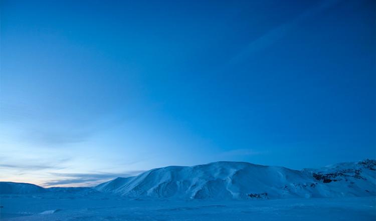 Berg i ett isländskt vinterlandskap upplysta av månljus
