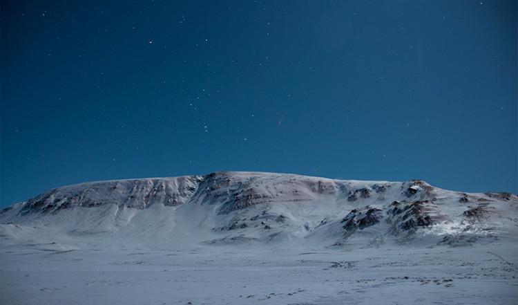Snöklädda berg endast upplyst av månen en stärnklar natt, Island
