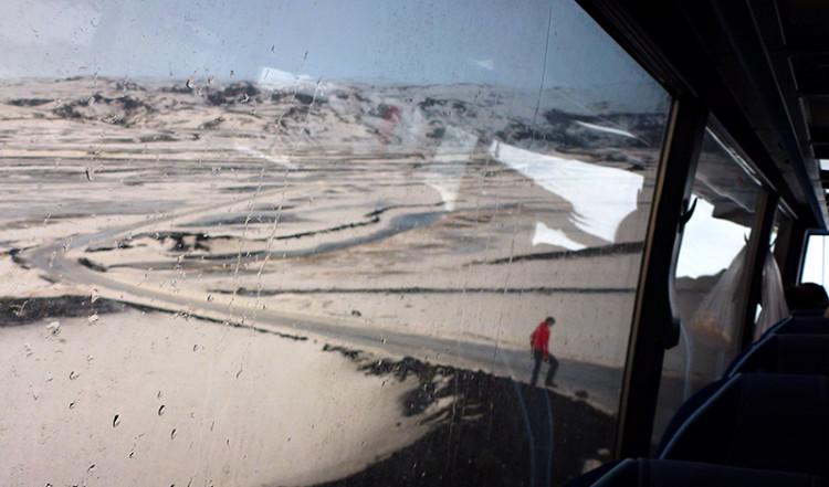 Guiden plockar bort sten från väg, Island