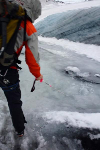 Guiden leder undan smältvatten på glaciären Sólheimajökull, Island