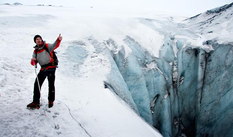 Guiden vid djupt hål i glaciären vid Sólheimajökull, Island