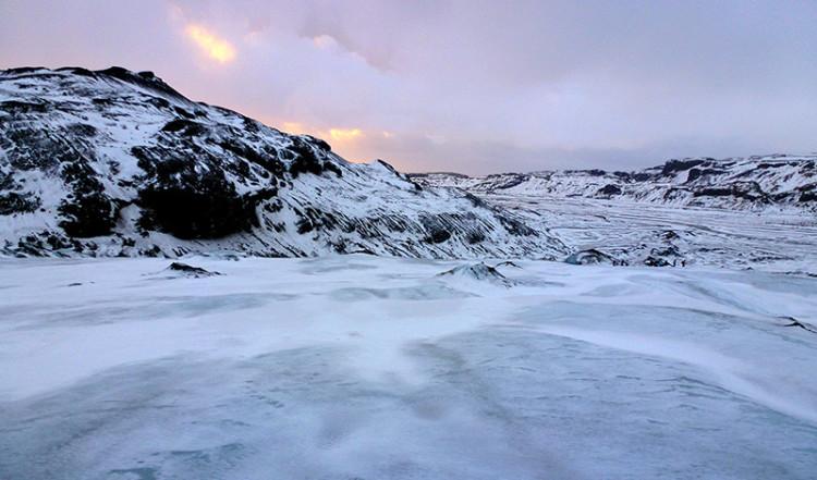 Vintersolen färgar himlen Sólheimajökull, Island