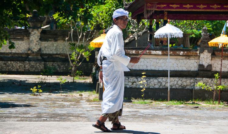 Präst på väg in till tempel utmed Sanur strandpromenad, Bali