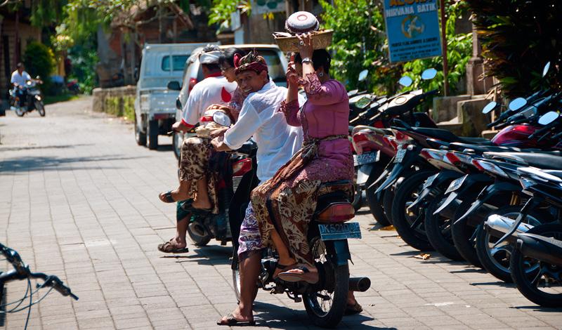 Kvinnor med mat på huvudet på mopeder, Ubud Bali