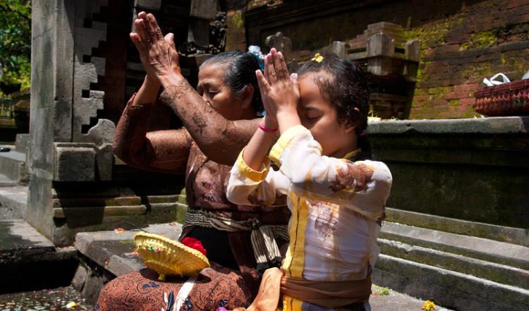 En äldre kvinna och ung flicka ber tillsammans, Tirtha Empul Tempel, Bali