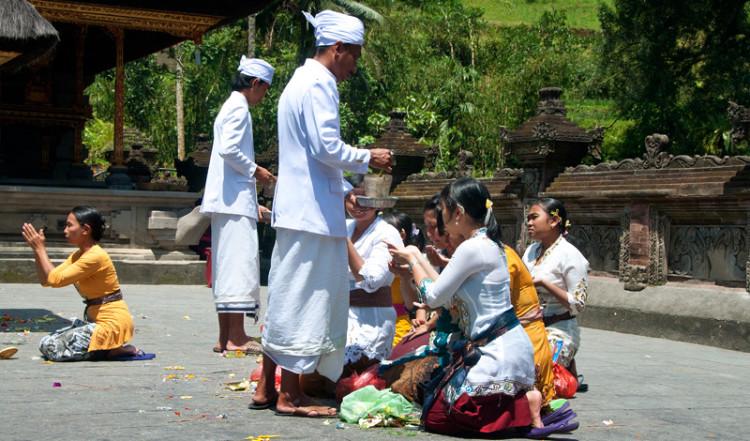 Män skvätter vatten på bedjande kvinnor vid Pura Tirtha Empul, Bali