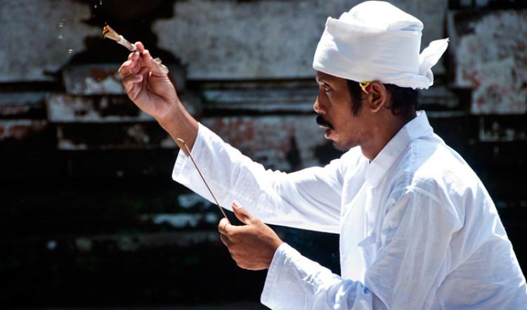 Man skvätter iväg vatten i samband med bön vid Gunung Kawi tempel, Bali