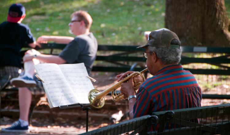 En man spelar trumpet i Central Park, New York