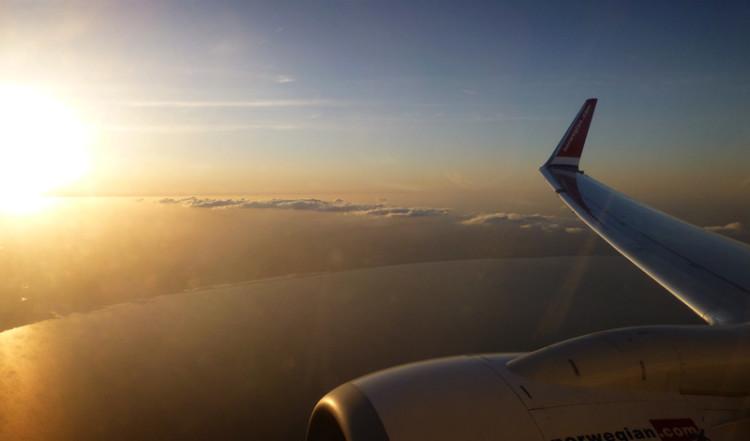 Solnedgång från molnen i ett Norwegian plan mot Spanien