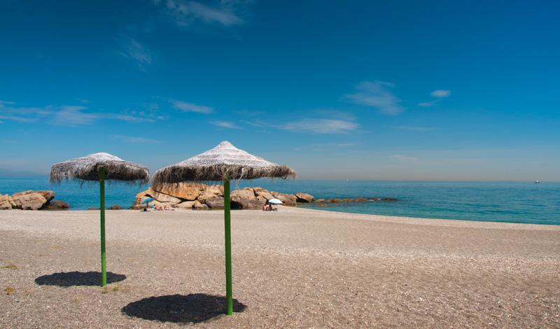 Parasoller på stranden vid Punta Chullera