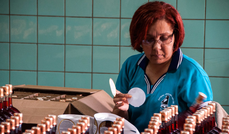 Etiketterna på flaskorna klistras på för hand innan de paketeras ner i lådor på likör fabriken i Willemstad, Curacao