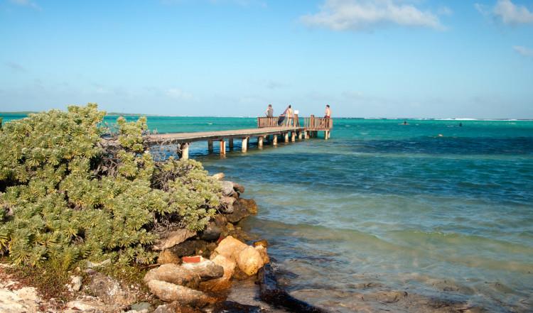 Eftermiddagssol över bryggan och stranden till Sorobon Beach Resort på Bonaire