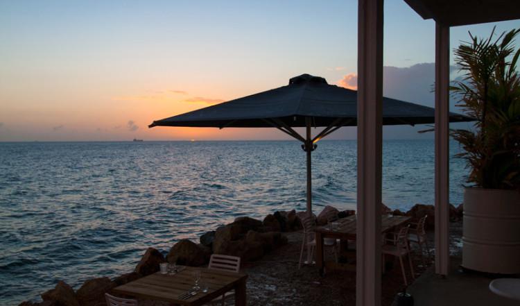 Solnedgång efter att himmeln öppnat upp sig över havet och Bijblauw Hotel i Willemstad