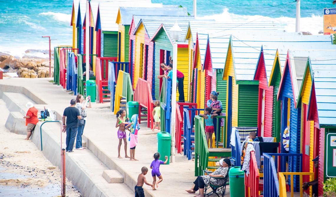 Färgglada strandhus utmed kustvägen och False Bay i Sydafrika