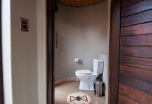 Ifrån badrumsdelen finns en dörr in till toaletten på Thanda Safari Lodge