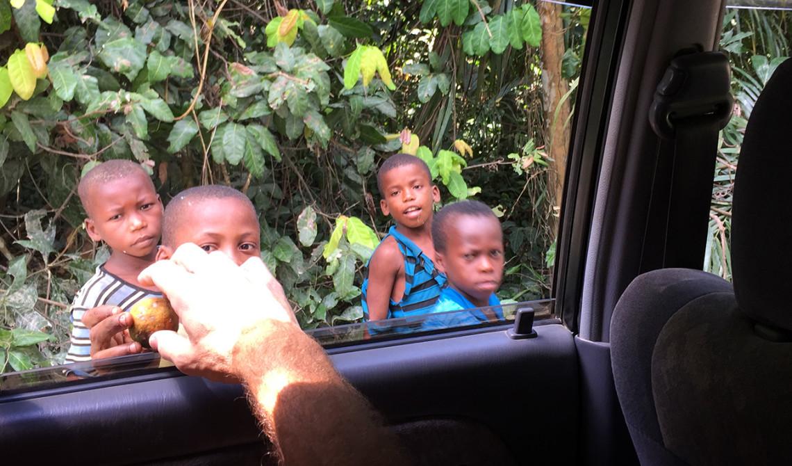 Småkillar ger oss frukt från djungel