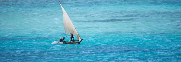 Båt som passerar ute i havet utanför stranden till Manta Resort