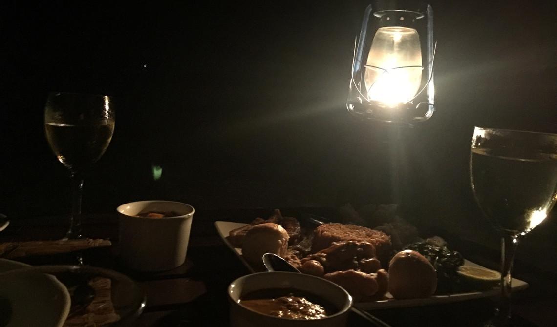 Middag på stranden med fotogenlampa och stjärnorna på himmeln som enda ljus