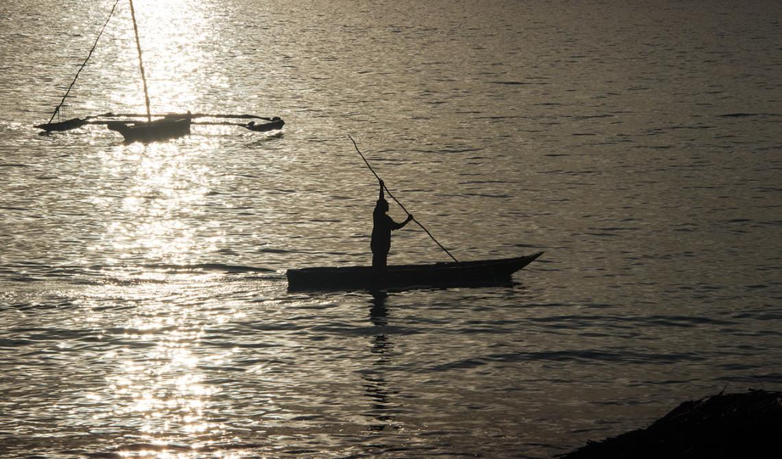 Man i båt passerar i vattnet under solnedgången