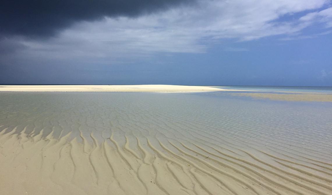 Blandat sol och moln över sandbanken