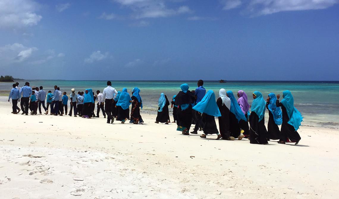 Skolklass från stan besöker Manta Resort och promenerar längst med den vackra stranden