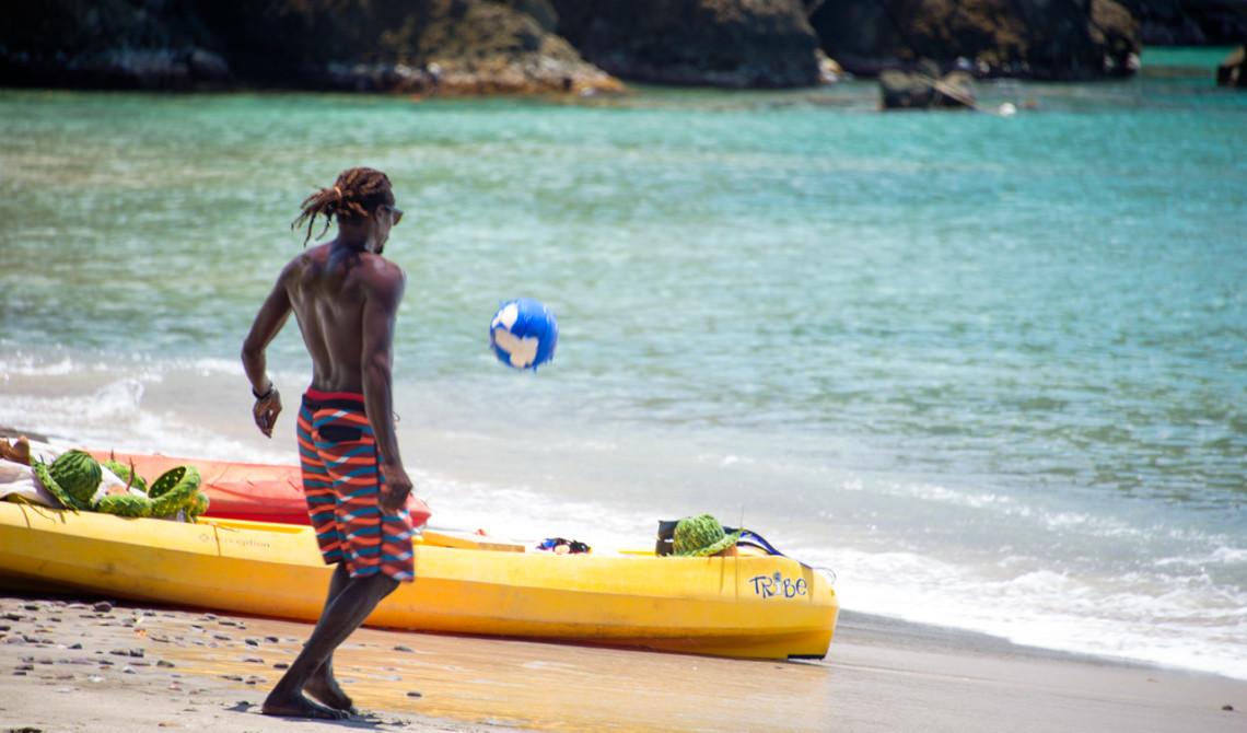 Lokal kille spelar fotboll på stranden vid Ti Kaye Resort & Spa, Saint Lucia