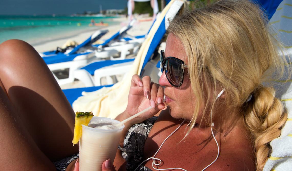 Anki njuter av en Piña Colada på stranden till Windsong Resort, Turks & Caicos