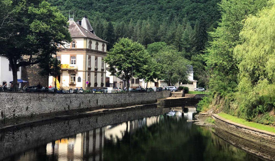 Vy över floden och en bit av den lilla stan Esch-sur-Sûre i Luxemburg