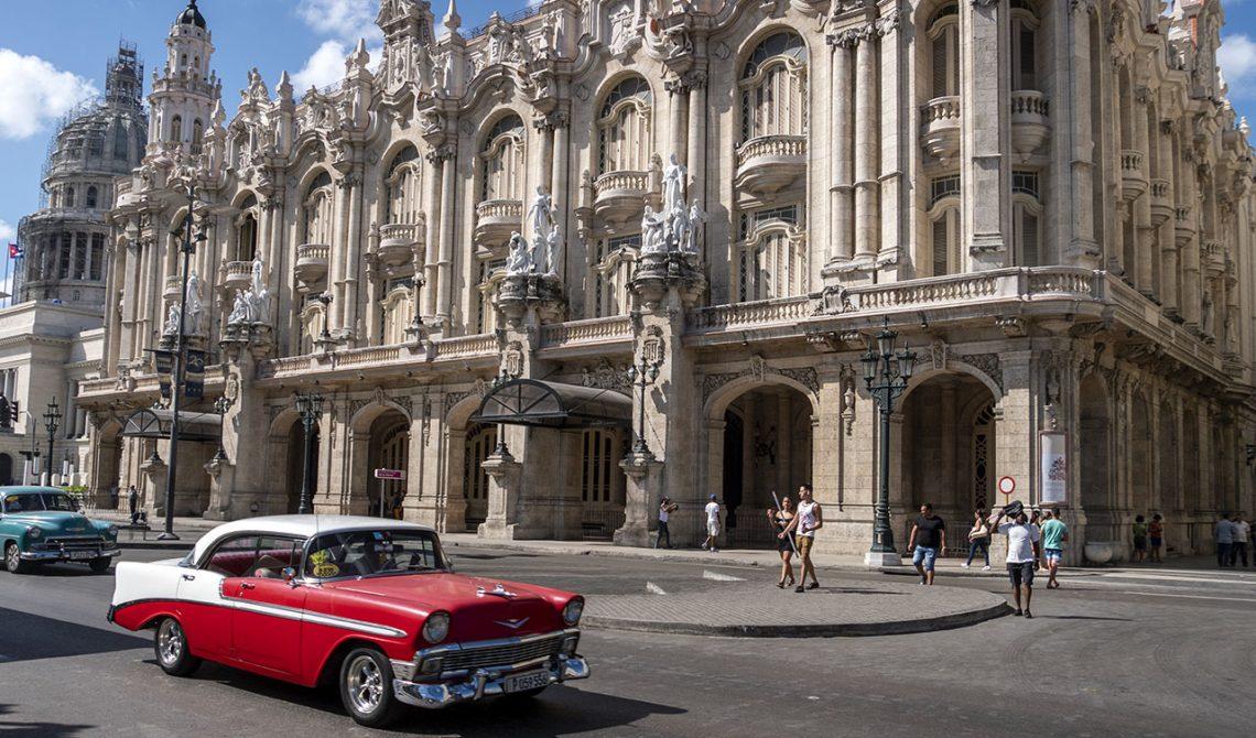 Klassisk röd gammal bil längst med gatorna vid vid Parque Central i centrala Havanna