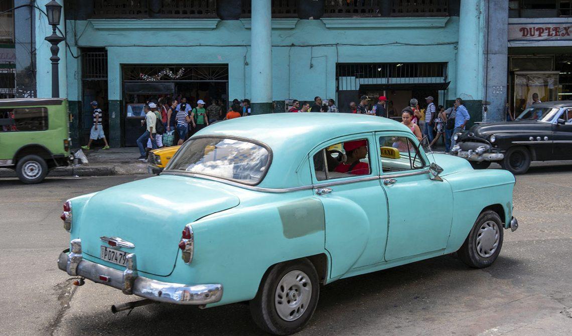 Turkos bil passerar en matchande turkos byggnad i Havanna