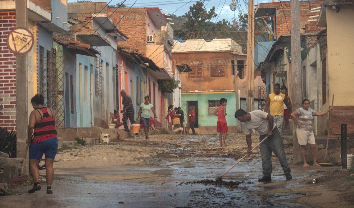 På väg in i Trinidad har det regnat och folk sopar bort vatten från gatorna