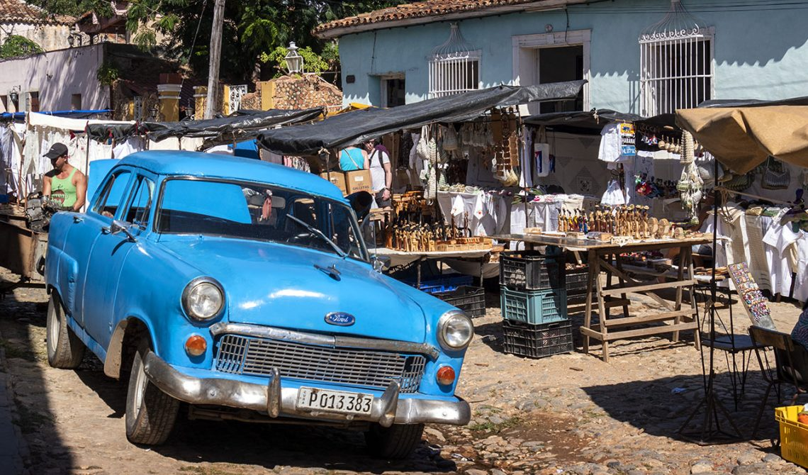 Blue old car parked by a market in Trinidad, Cuba